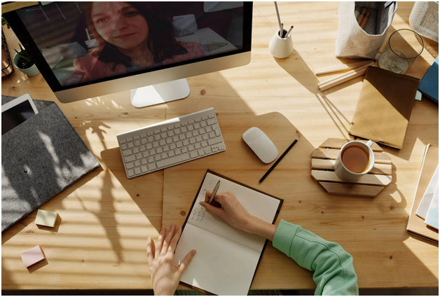 A person is utilizing distance learning at their desk with coffee