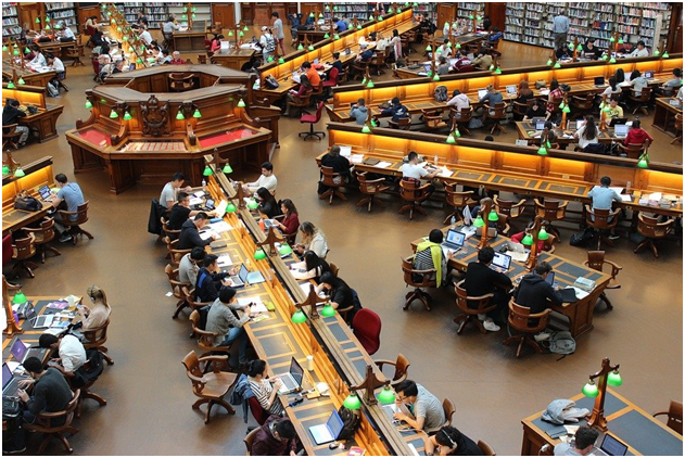 A library with lots of students studying for exams