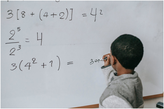 Child solving math problems on a board